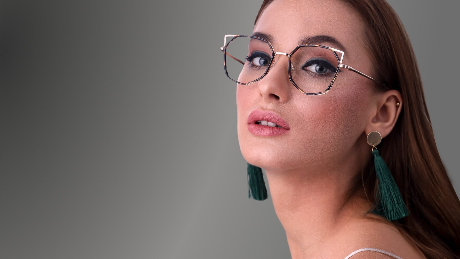 Young woman with glasses brown hair and green earrings