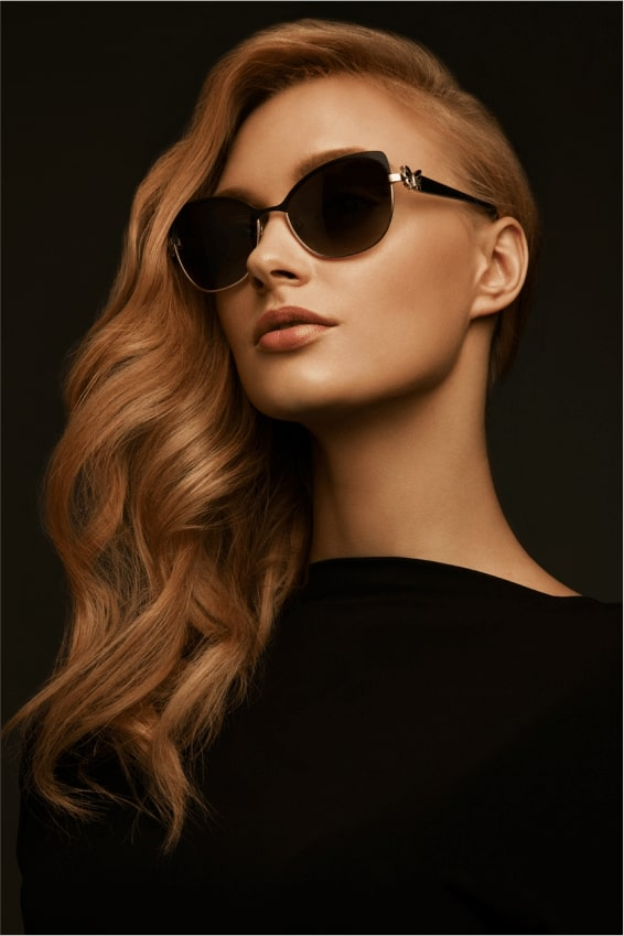 Blonde woman with dark sunglasses on black background
